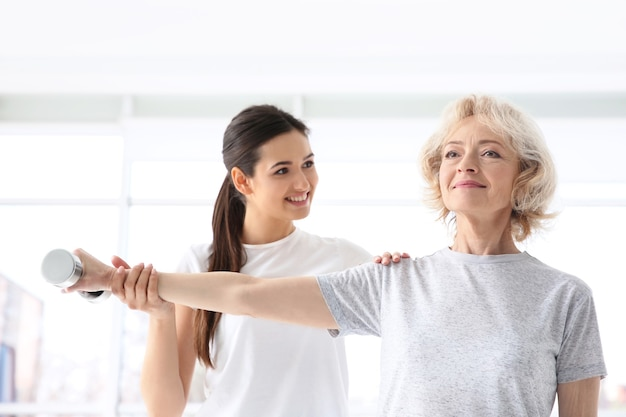 Physiothérapeute travaillant avec un patient âgé dans une clinique moderne