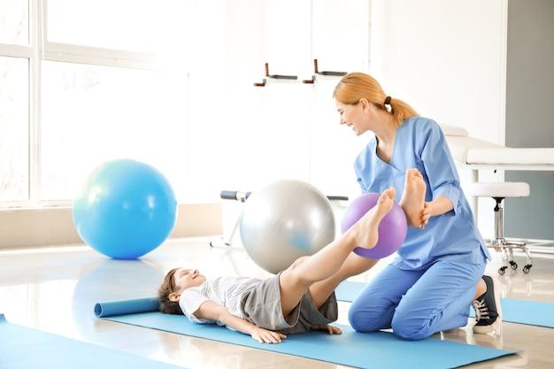 Physiothérapeute travaillant avec petit garçon dans un centre de réadaptation
