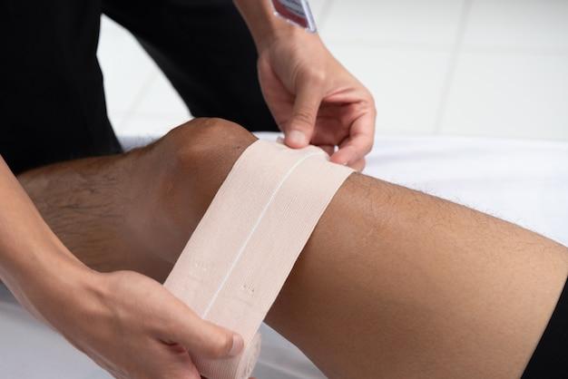 Les physiothérapeutes utilisent les poignées de la jambe du patient pour s'allonger sur le lit dans une salle médicale.