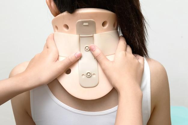 Physiothérapie mettant le collier philadelphia sur le patient du cou