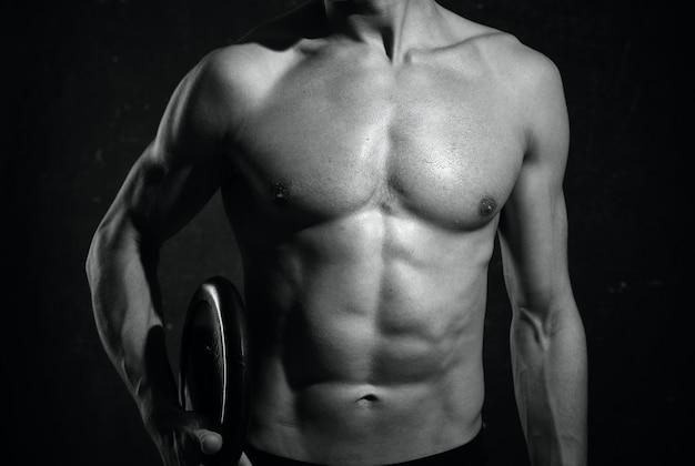Physique athlétique masculin recadrée vue muscle fond sombre