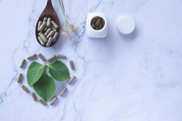 Phytothérapie en capsules sur une cuillère en bois avec une feuille verte naturelle sur du marbre blanc
