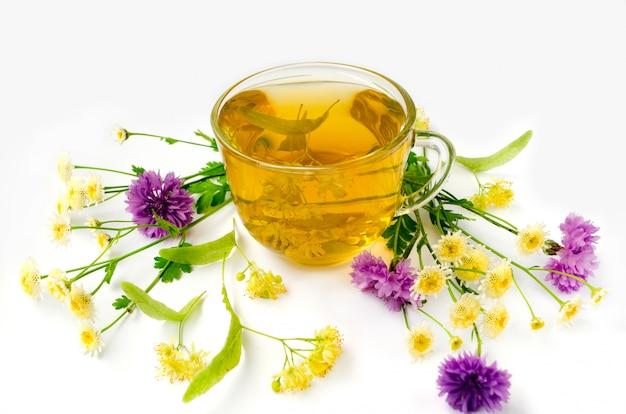 Phytothérapie. tasse de thé de tilleul avec des fleurs de camomille et de bleuet. thé au tilleul