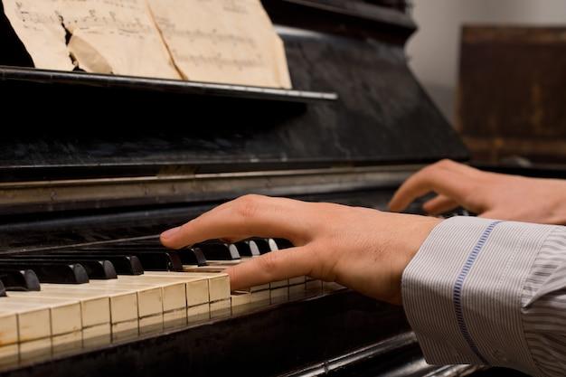 Pianiste masculin pratiquant assis à un piano droit jouant de la musique à partir d'une vieille feuille de partition