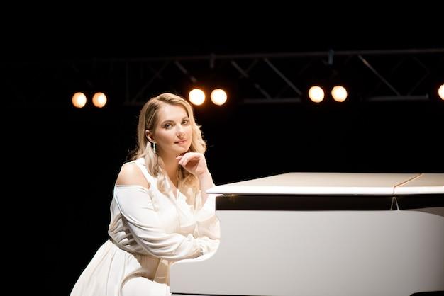 Pianiste posant près de piano blanc sur la scène