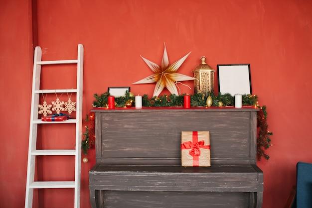 Un piano avec des décorations de noël dessus et un escalier blanc dans la maison sur un mur rouge