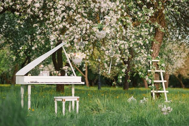 Piano à queue blanc et escalier blanc au décor romantique au printemps dans un jardin de pommiers en fleurs