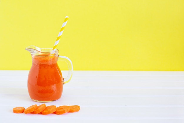 Pichet de jus de carotte biologique et carotte fraîche sur fond de couleur. alimentation saine de désintoxication, régime alcalin. concept de nourriture d'été.