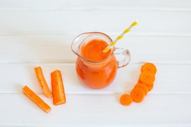 Pichet de jus de carotte et carottes fraîches sur fond blanc.