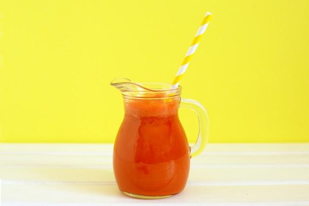 Pichet de jus de carotte avec tube à cocktail sur la couleur