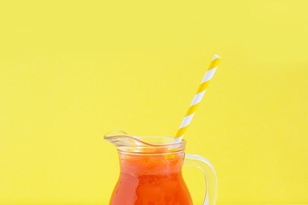 Pichet de jus de carotte avec tube à cocktail sur fond jaune. alimentation saine de désintoxication, régime alcalin. concept de nourriture d'été.
