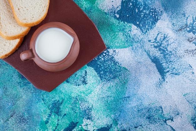 Un pichet de lait frais avec du pain blanc tranché sur un plateau brun.