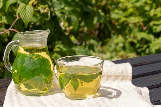 Un pichet transparent et une tasse de thé vert et de feuilles de cassis et de menthe