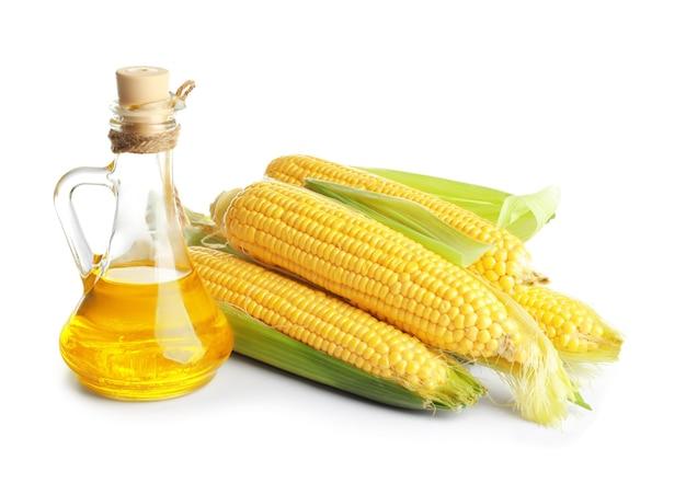 Pichet en verre avec de l'huile de maïs et des épis mûrs sur blanc