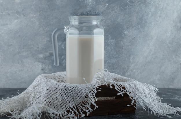Pichet en verre de lait dans une boîte en bois avec de la toile de jute.