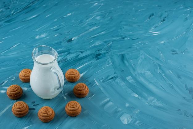 Un pichet en verre de lait frais avec des biscuits ronds sucrés sur fond bleu.