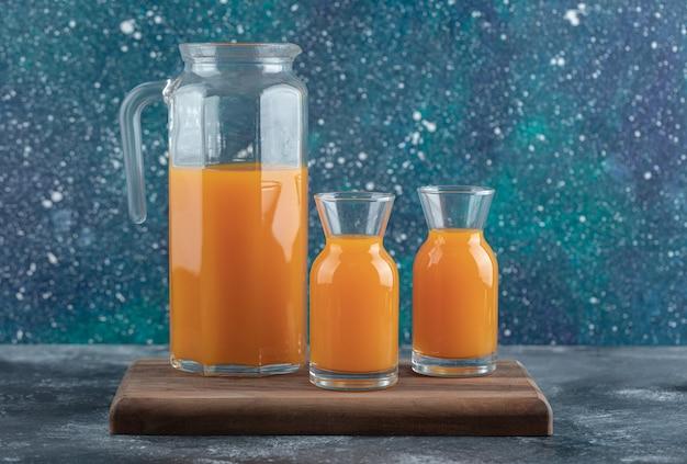 Pichet et verres de jus d'orange sur planche de bois.