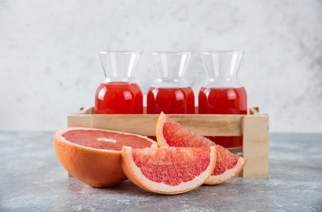 Pichets en verre de jus de pamplemousse frais dans une boîte en bois avec des tranches de fruits.
