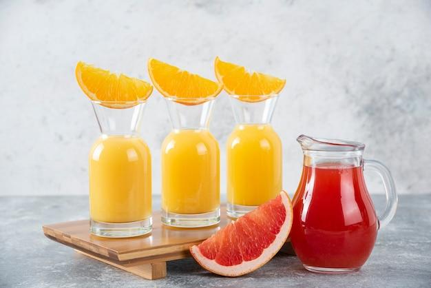 Pichets en verre de jus de pamplemousse avec des tranches de fruits orange.
