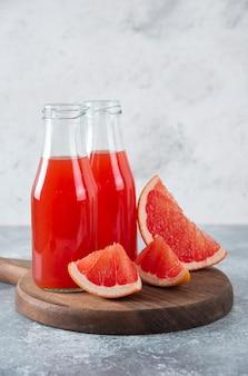 Pichets en verre de jus de pamplemousse avec des tranches de fruits.