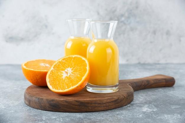 Pichets en verre de jus avec tranche de fruit orange.