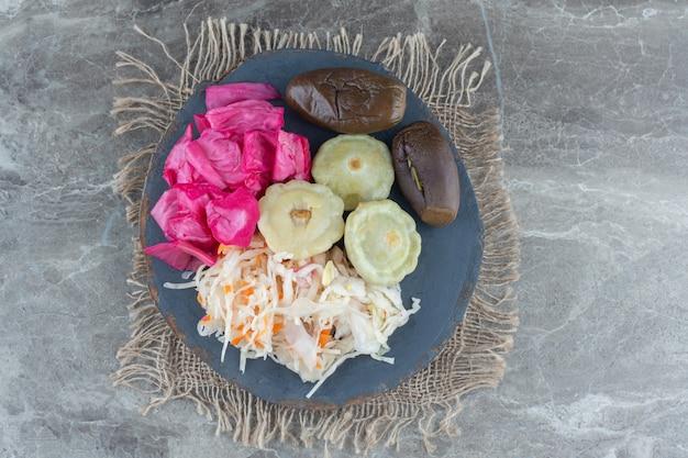 Pickle de légumes hachés sur planche de bois sur table grise.