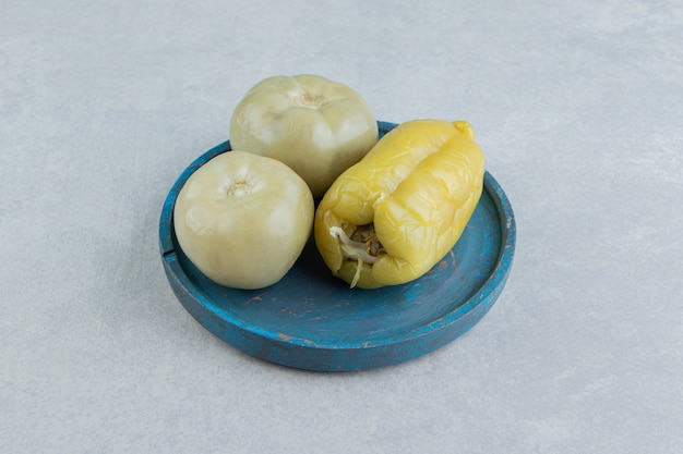 Pickles tomates et poivrons sur une plaque en bois, sur la surface en marbre