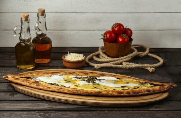 Pide traditionnel turc aux herbes et fromage sur une planche de bois