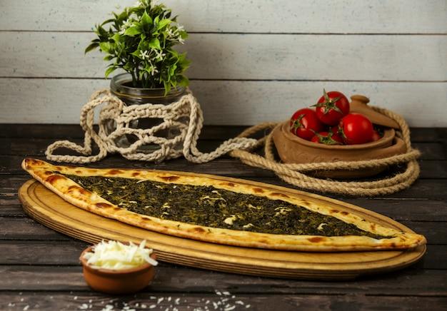 Pide traditionnel turc avec du fromage et des herbes sur une planche de bois