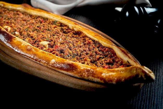Pide turc avec agneau haché, tomates, poivron servi sur plateau en bois. table noire