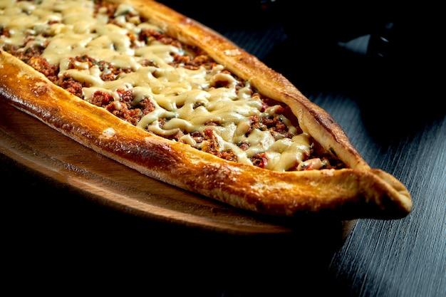 Pide turc avec agneau haché, tomates, poivrons et fromage cheddar sur une table noire