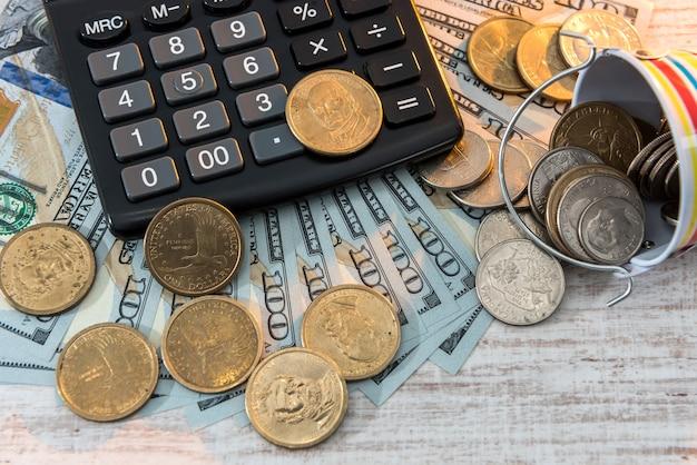Pièce de 1 dollar américain avec calculatrice couchée sur fond de billets d'un dollar. concept d'argent