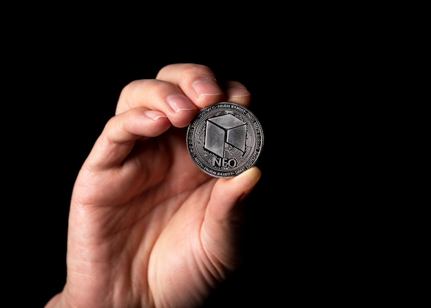 Pièce d'argent brillant neo dans la main masculine sur fond noir.