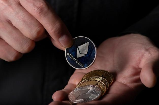 Pièce d'argent ethereum de crypto-monnaie dans la paume de la main masculine sur fond noir, gros plan. eth mis en pile crypto.