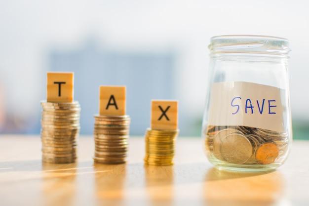 Pièce d'argent sur la table en bois et texte, taxe, économiser, arrière-plan flou.
