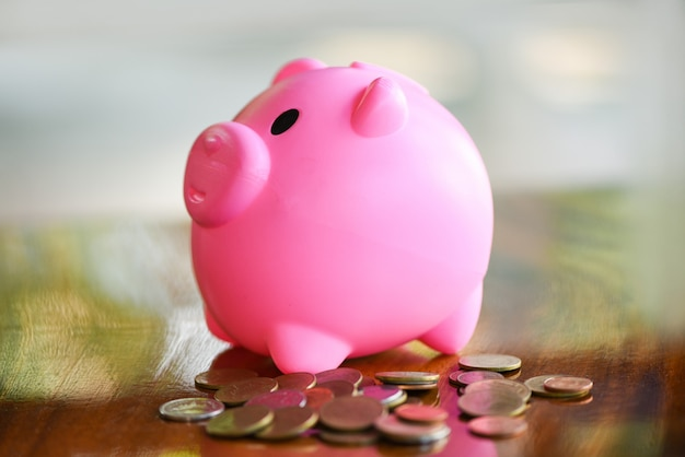 Pièce d'argent et tirelire rose à table à la maison se bouchent - économiser de l'argent pour le concept de bourses
