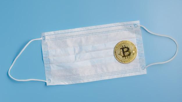 Pièce de bitcoin et masque chirurgical de protection sur fond bleu. concept d'épidémie de virus épidémique. équipement de protection contre les coronavirus.