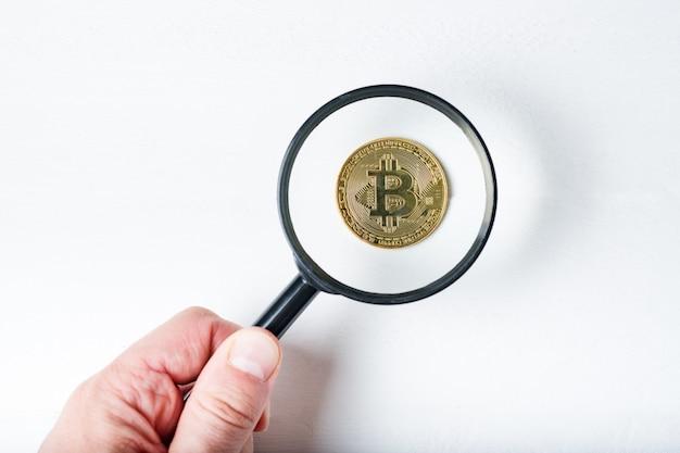 Pièce de bitcoin à travers une loupe