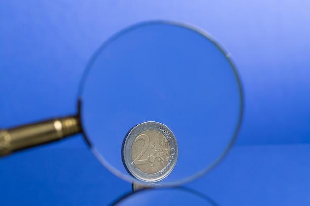 Pièce de deux euros sur fond bleu à travers une loupe avec une belle réflexion