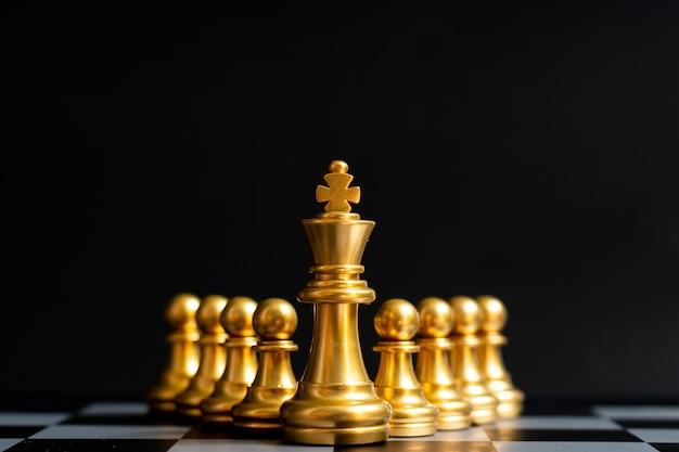 Pièce d'échecs du roi d'or se tenir devant un pion sur fond noir (concept de leadership, gestion)