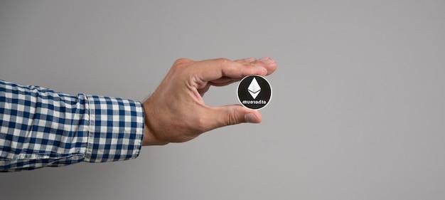 Pièce d'ethereum dans la main de l'homme sur fond gris. concept de monnaie crypto.