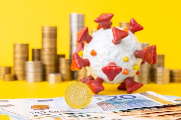 Une pièce d'un euro et d'autres billets de l'ue en gros plan, modèle de coronavirus et des piles de pièces dans le