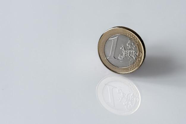 Une pièce en euro isolé sur une surface réfléchissante blanche