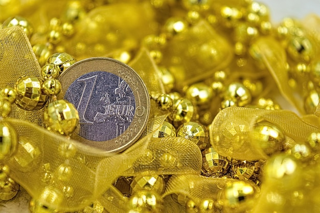 Une pièce en euro parmi les décorations jaunes du nouvel an et de noël.