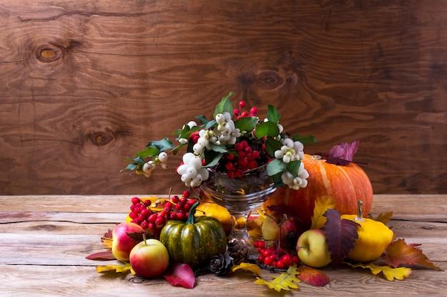 Pièce maîtresse de thanksgiving avec des baies de snowberry et de rowan dans un vase en verre,