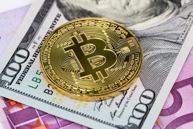 Pièce métallique bitcoin dorée sur les billets en dollars et en euros.