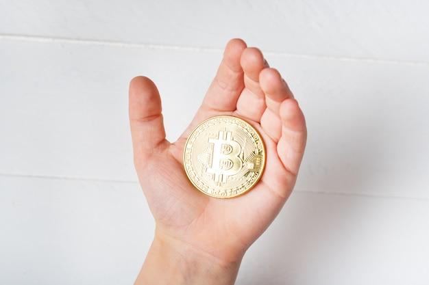 Pièce de monnaie bitcoin dans la main d'un enfant. fermer.
