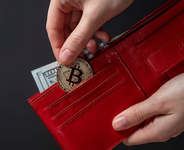 Pièce de monnaie bitcoin et dollars américains en portefeuille rouge sur fond noir, gros plan.