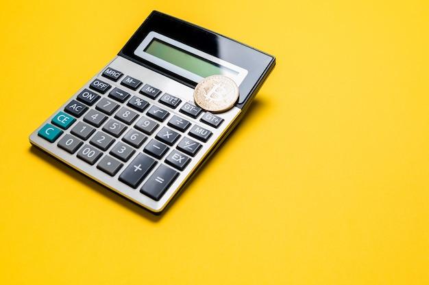 Pièce de monnaie bitcoin doré sur la calculatrice