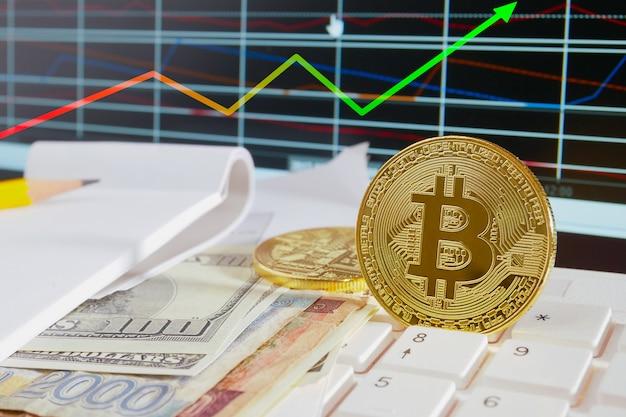 Pièce de monnaie en bitcoin dorée placée sur plusieurs billets et graphiques